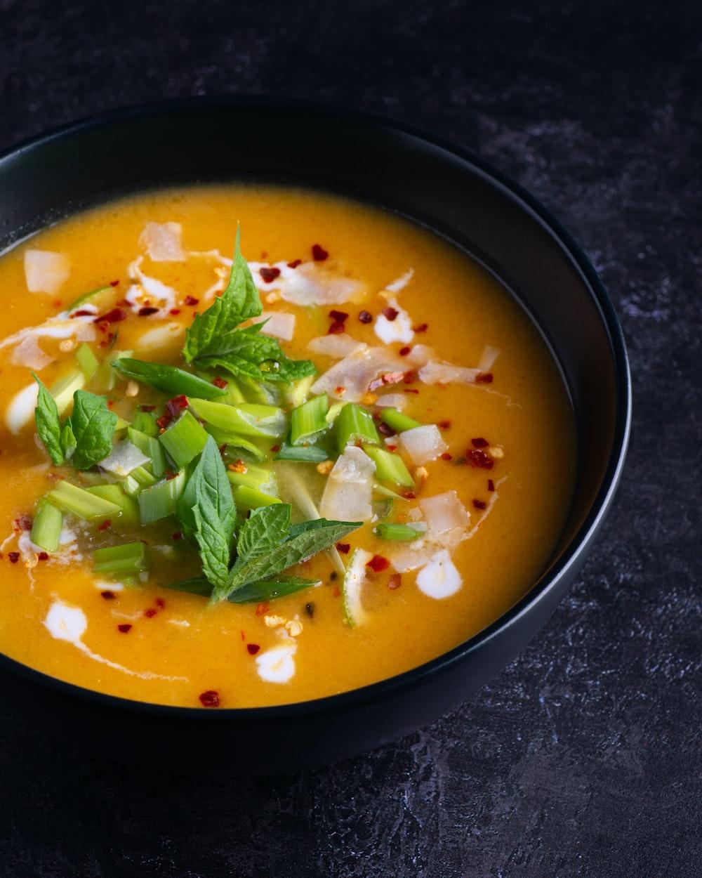 soup with green leaf on black ceramic bowl