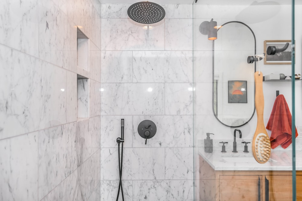 black shower head on white ceramic wall tiles