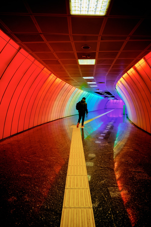 man in black jacket walking on tunnel