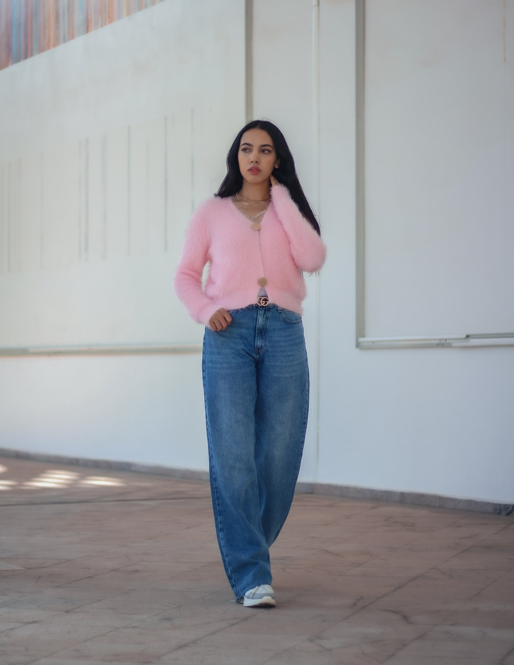 woman in pink long sleeve shirt and blue denim jeans standing near white wall