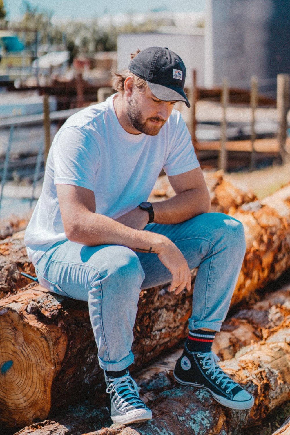man in blue t-shirt and blue denim jeans sitting on brown wood log during daytime