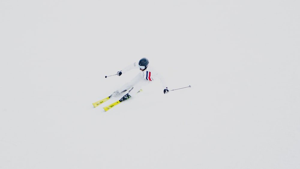 person in white and red suit riding yellow and white snowboard