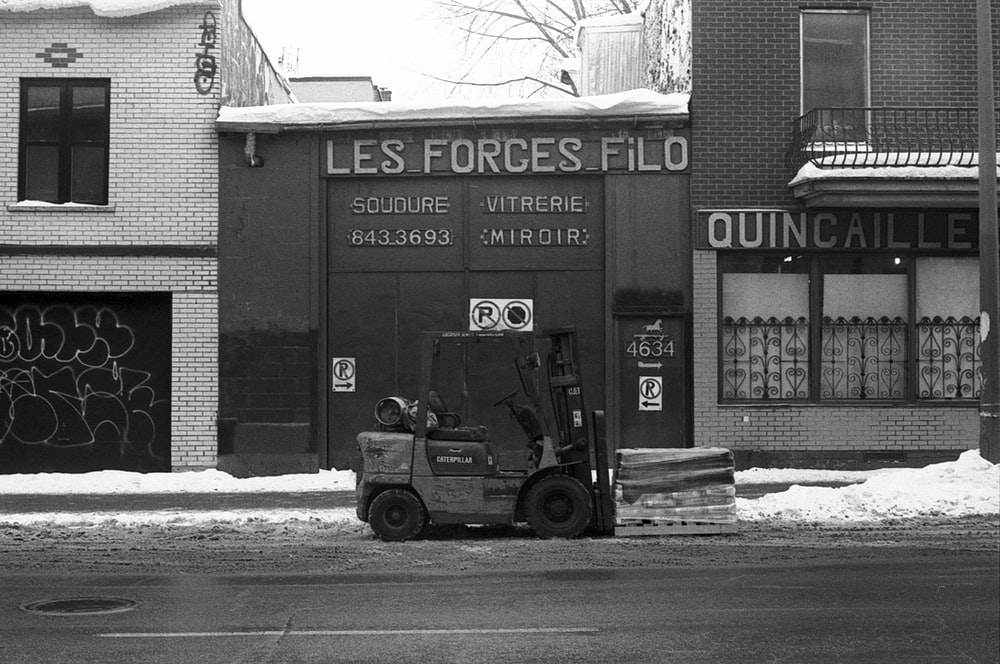 grayscale photo of a truck in front of a building