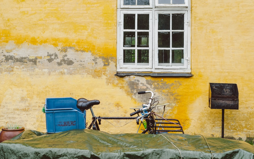 black and brown bicycle beside blue plastic box