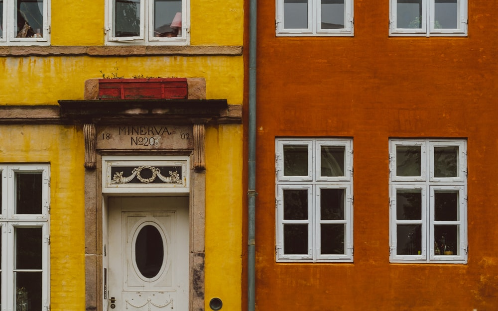 white wooden door on orange concrete building
