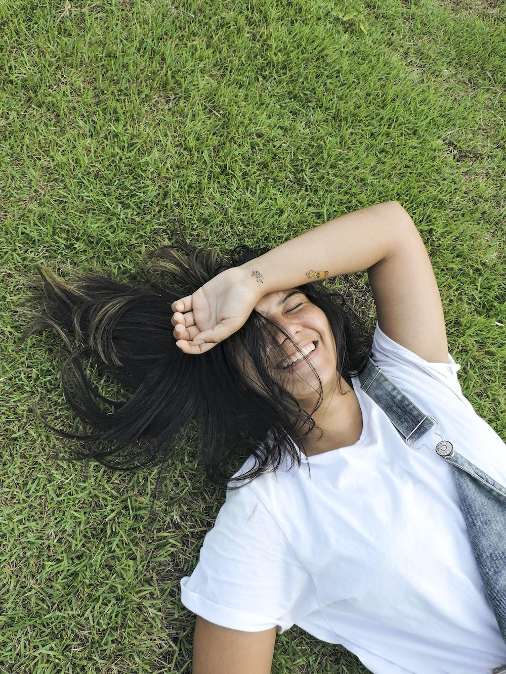 woman in white sleeveless shirt lying on green grass field