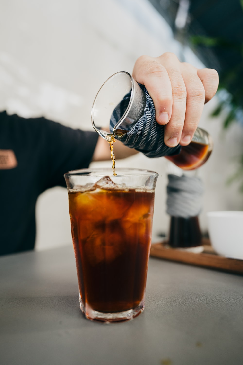 person pouring brown liquid on clear drinking glass