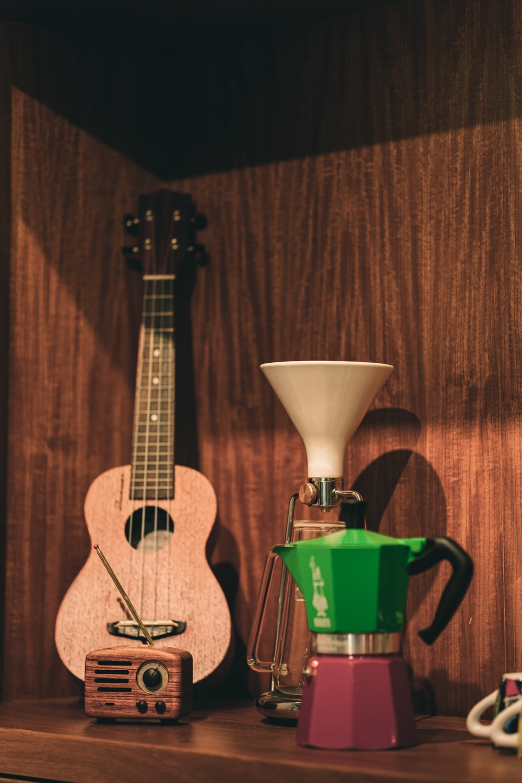 brown acoustic guitar beside green plastic cup