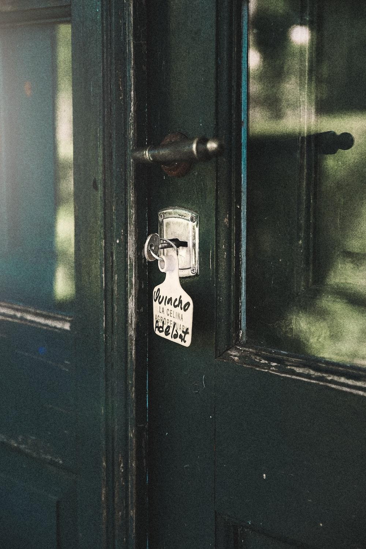 silver padlock on black wooden door