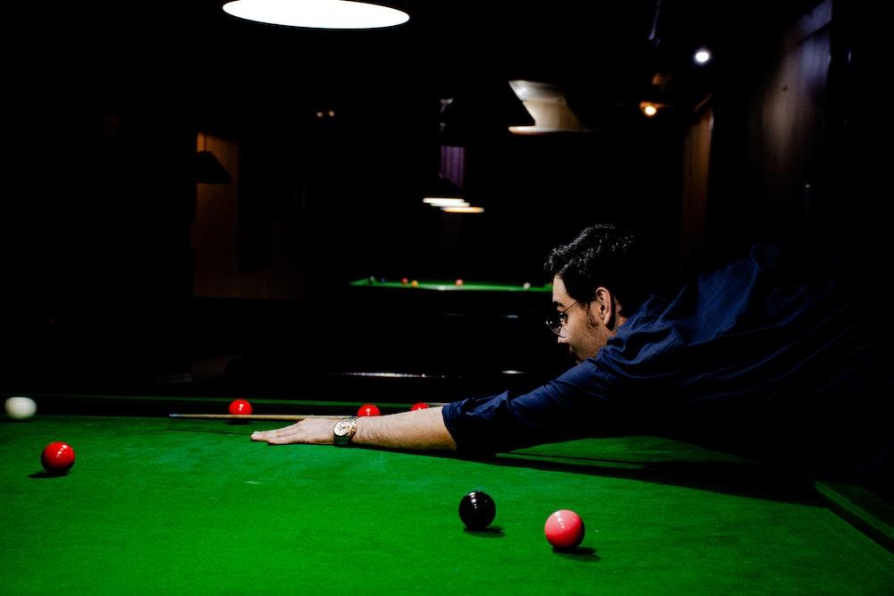 man in blue shirt playing billiard