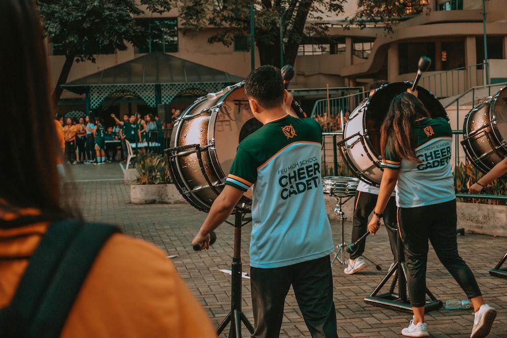 man in green crew neck t-shirt playing drum during daytime