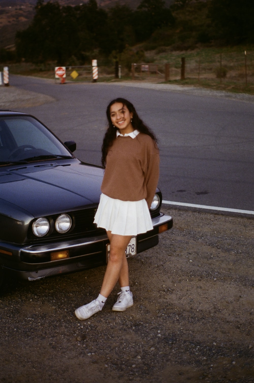 woman in brown long sleeve shirt and white skirt standing beside black bmw car