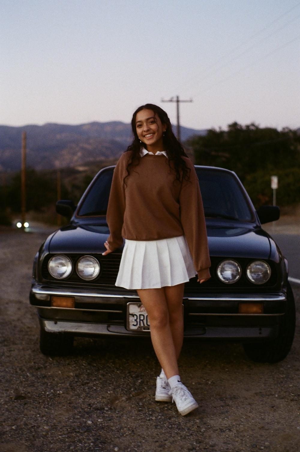 woman in brown long sleeve dress standing beside black car during daytime