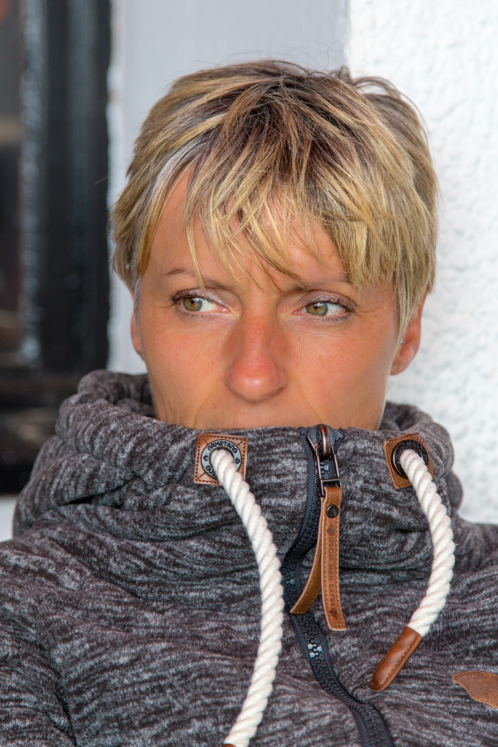 woman in gray sweater with black and white scarf