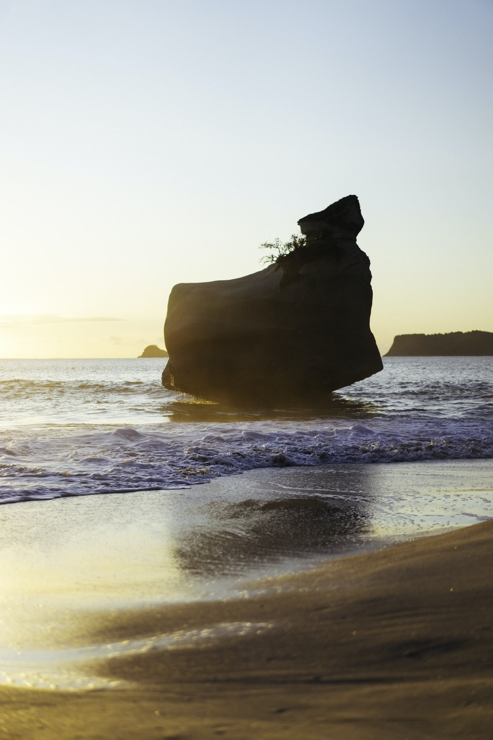 silhouette of rock formation on sea during daytime