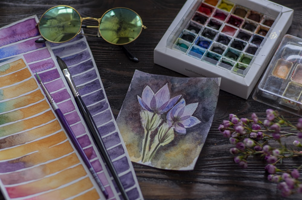 purple flower painting on brown wooden table