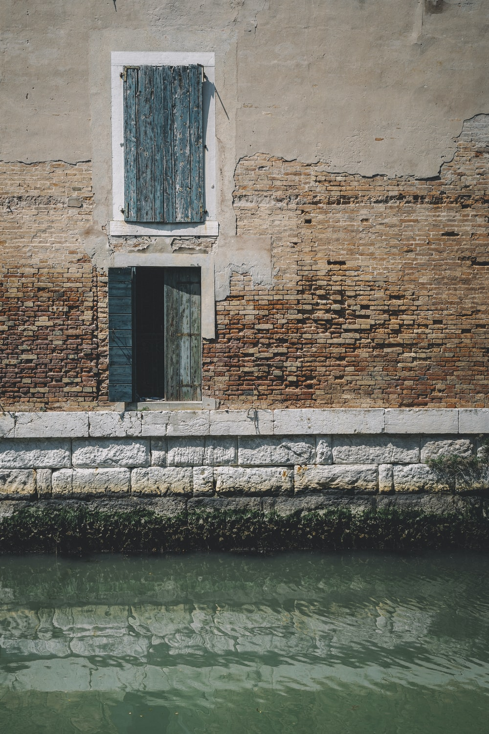 brown brick wall beside body of water during daytime
