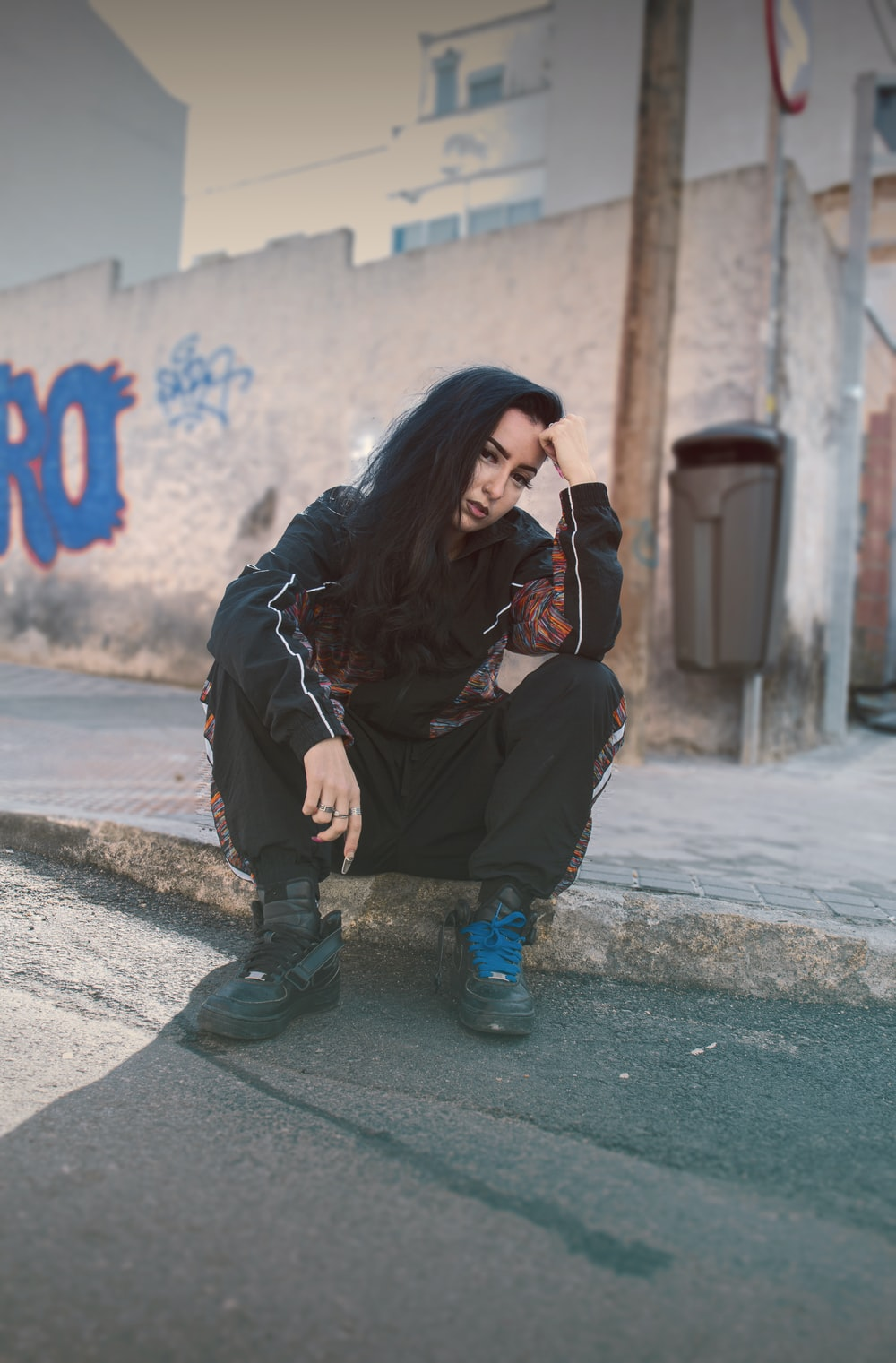 woman in black jacket and black pants sitting on concrete floor