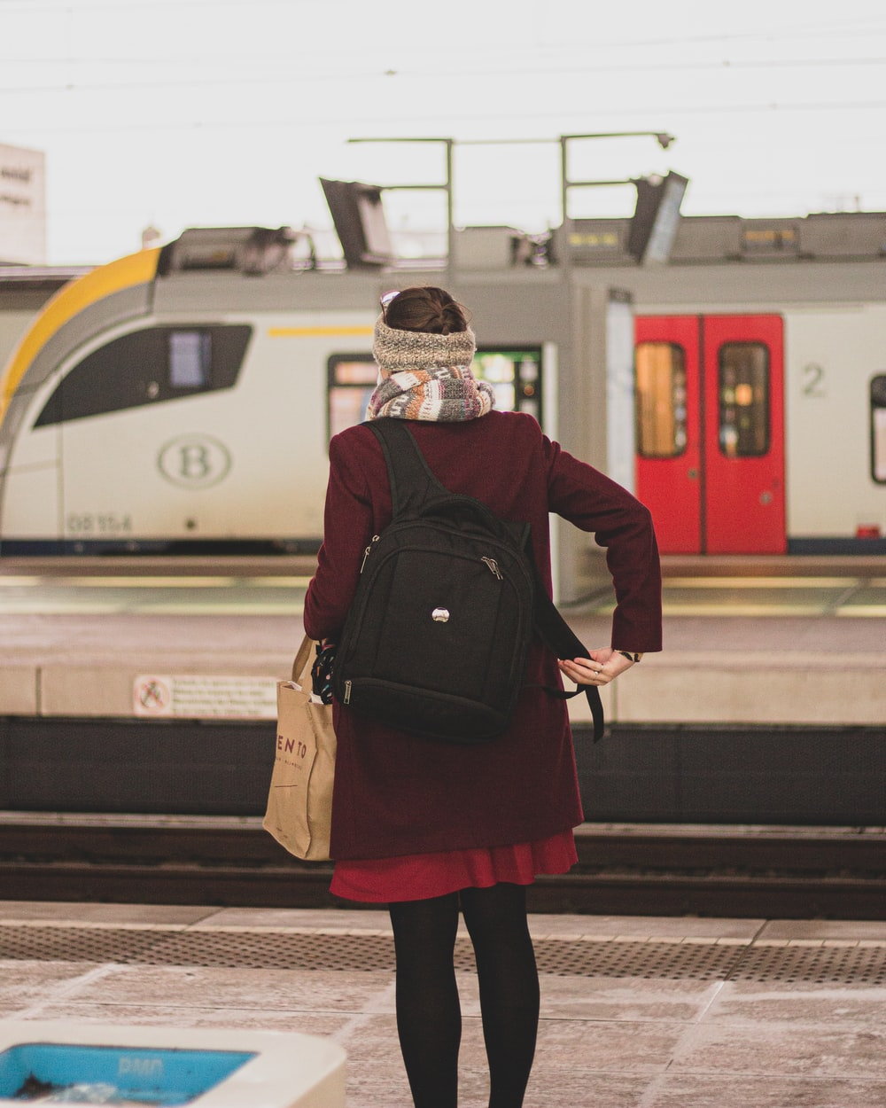 woman in black and red jacket standing on train station