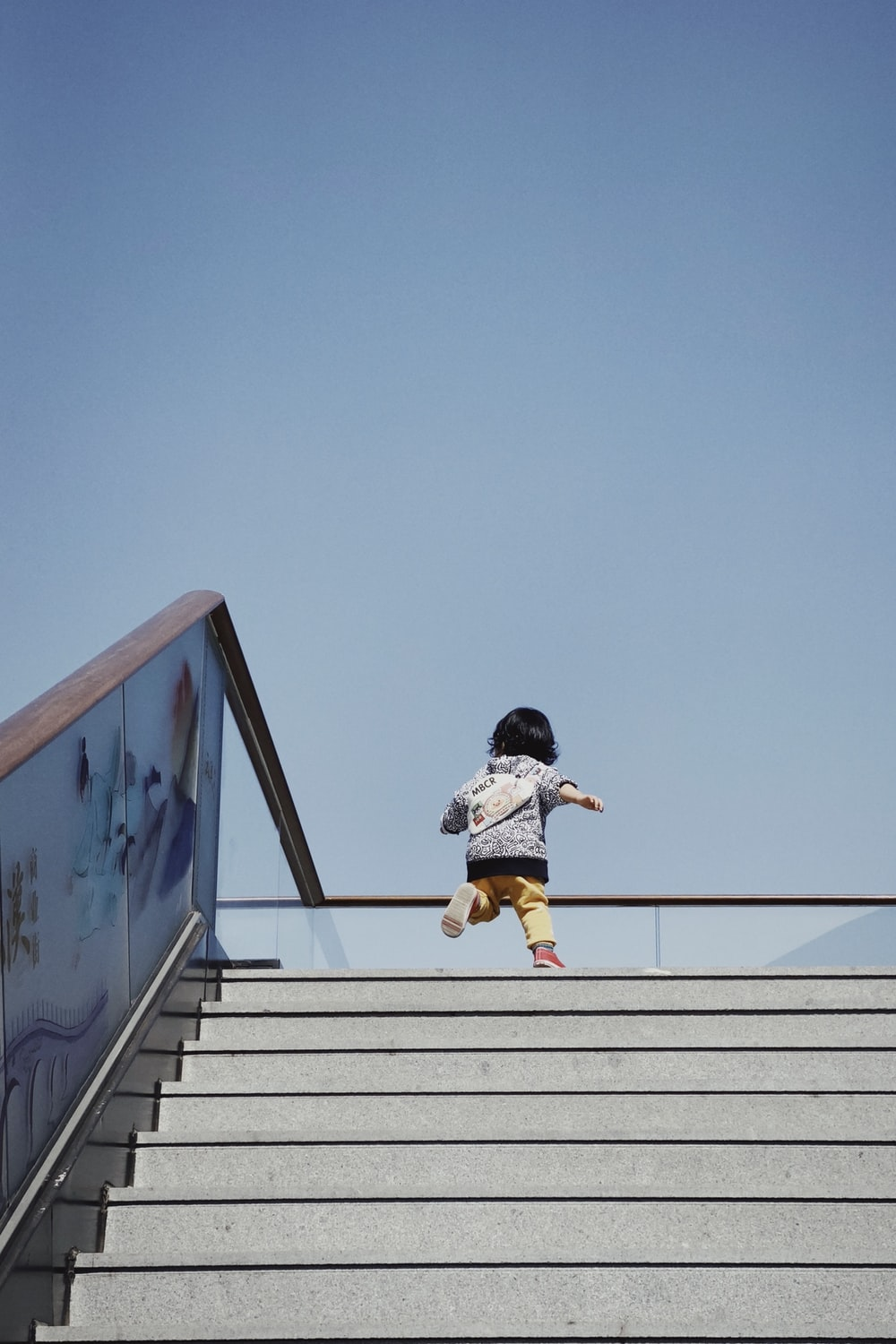 girl in white shirt and brown pants jumping on white concrete wall during daytime
