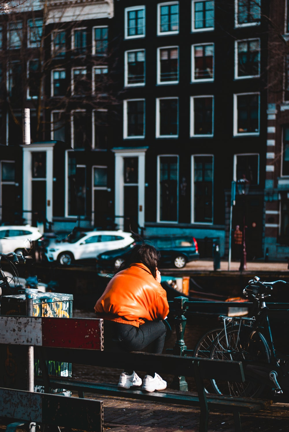 man in orange shirt sitting on bench in front of parked bicycle during daytime