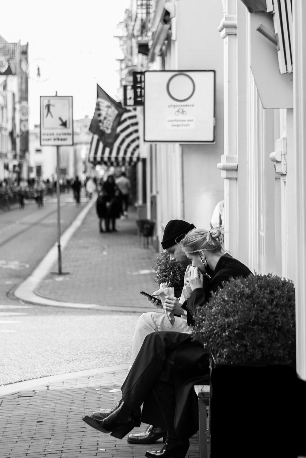 grayscale photo of woman in black jacket and black pants sitting on sidewalk