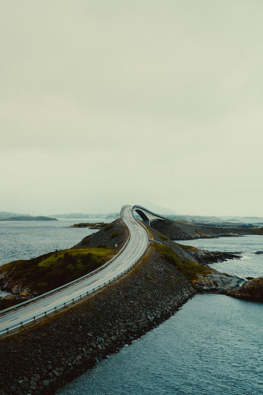 black asphalt road near body of water during daytime
