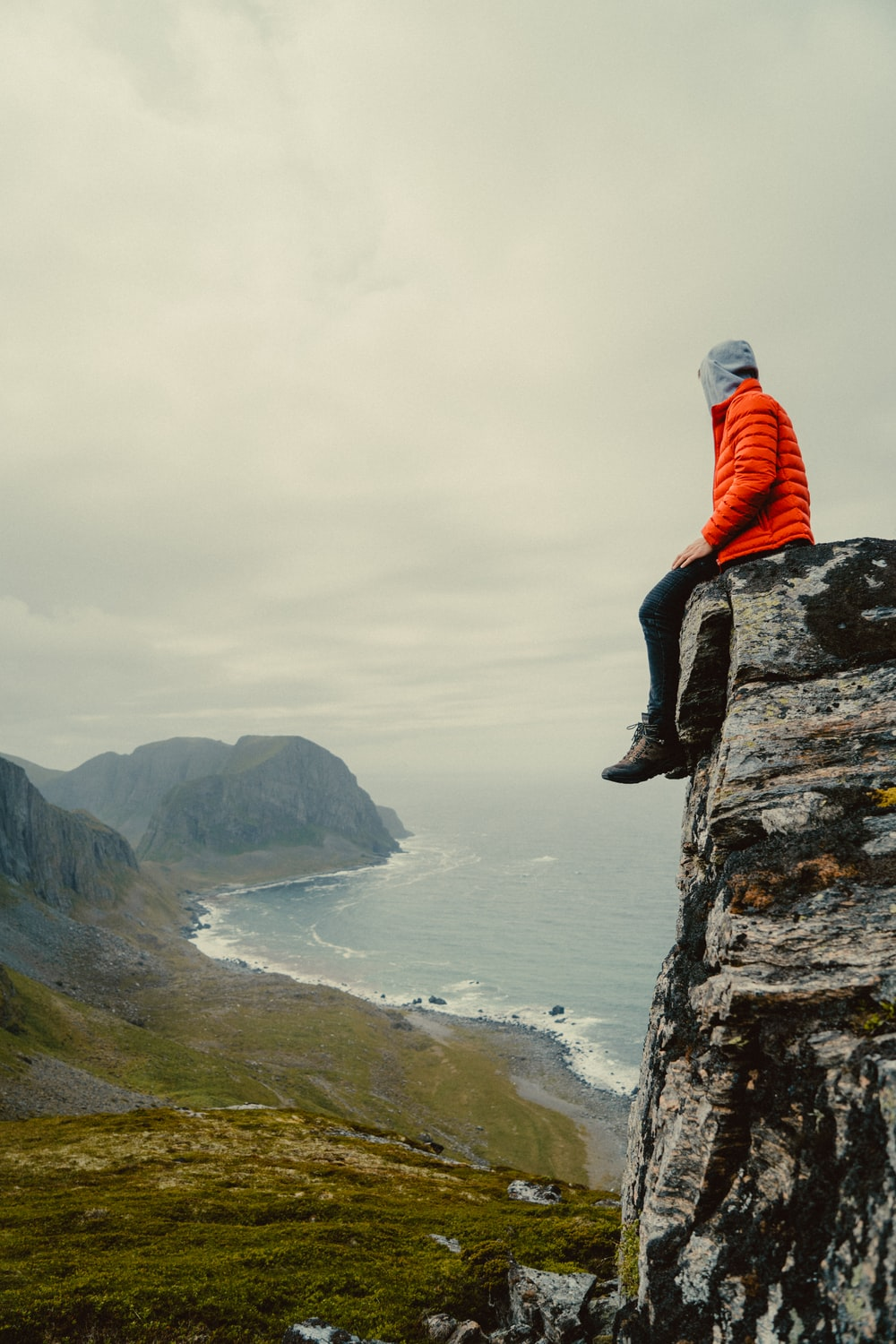 man in red hoodie sitting on rock formation near body of water during daytime