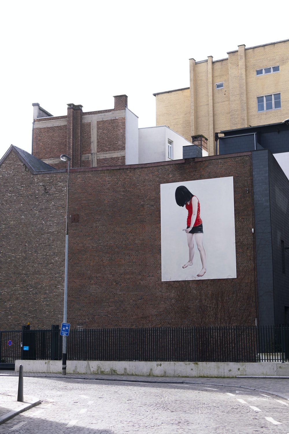 man in red and black jacket standing on gray concrete building during daytime