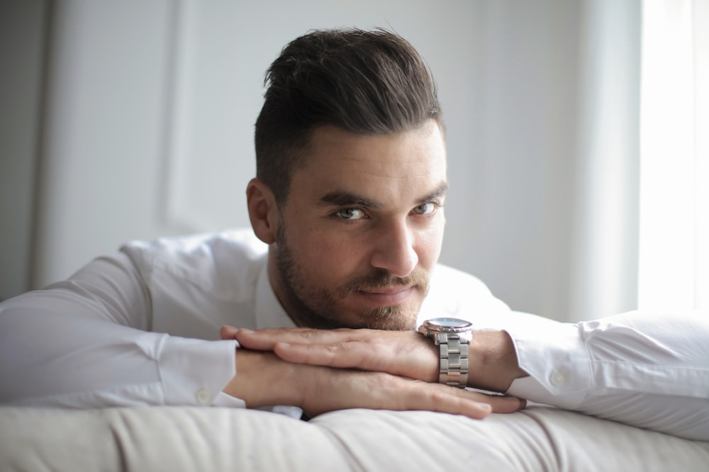 man in white dress shirt lying on bed