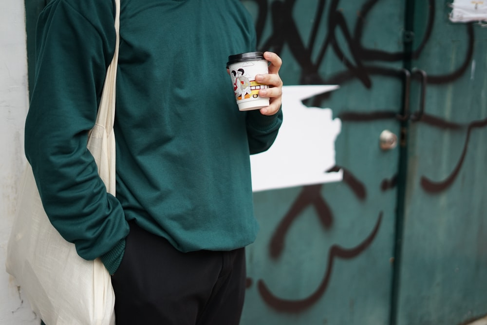 person in green sweater holding white ceramic mug