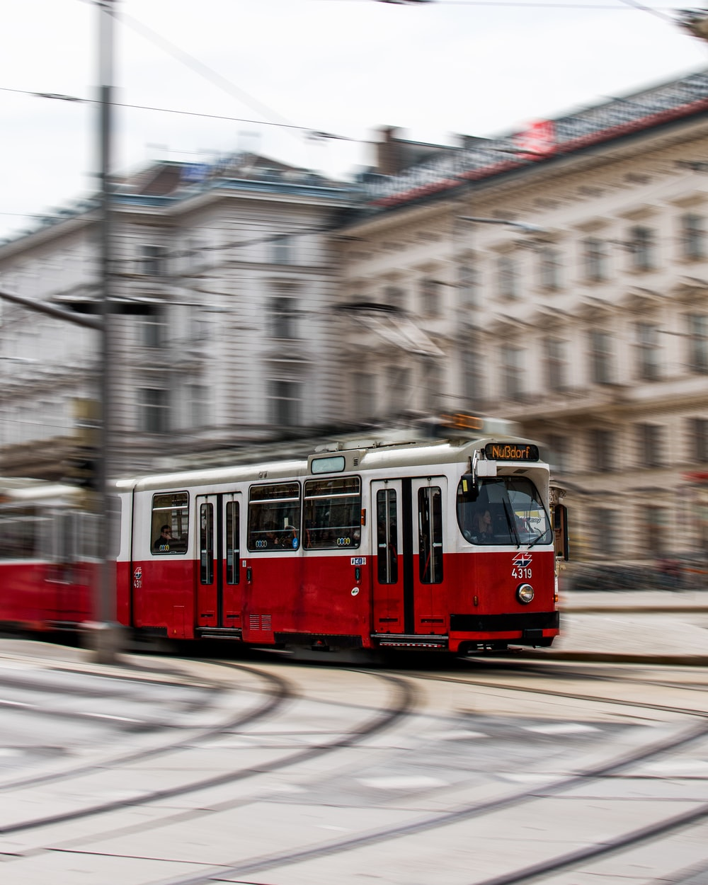 red tram on road near building during daytime