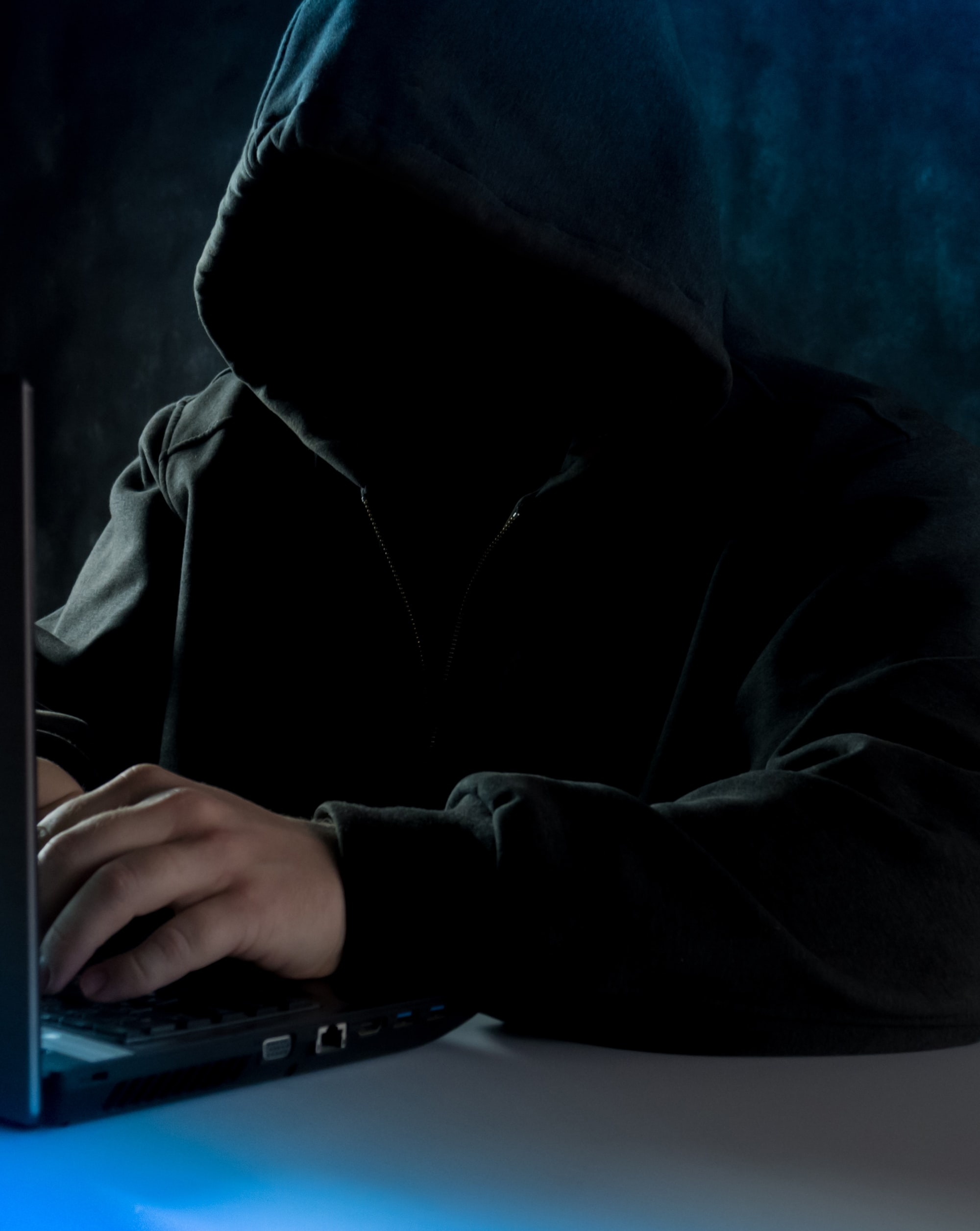 Anonymous computer hacker in hoodie. Using laptop computer for cyber attack and calling on cellphone.