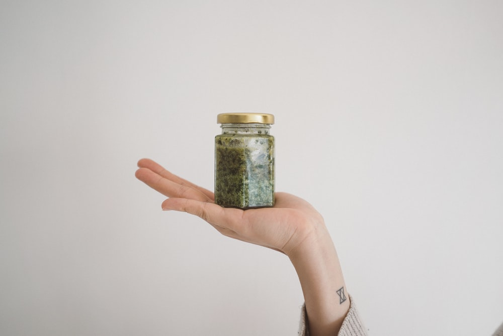 person holding green kush in glass jar