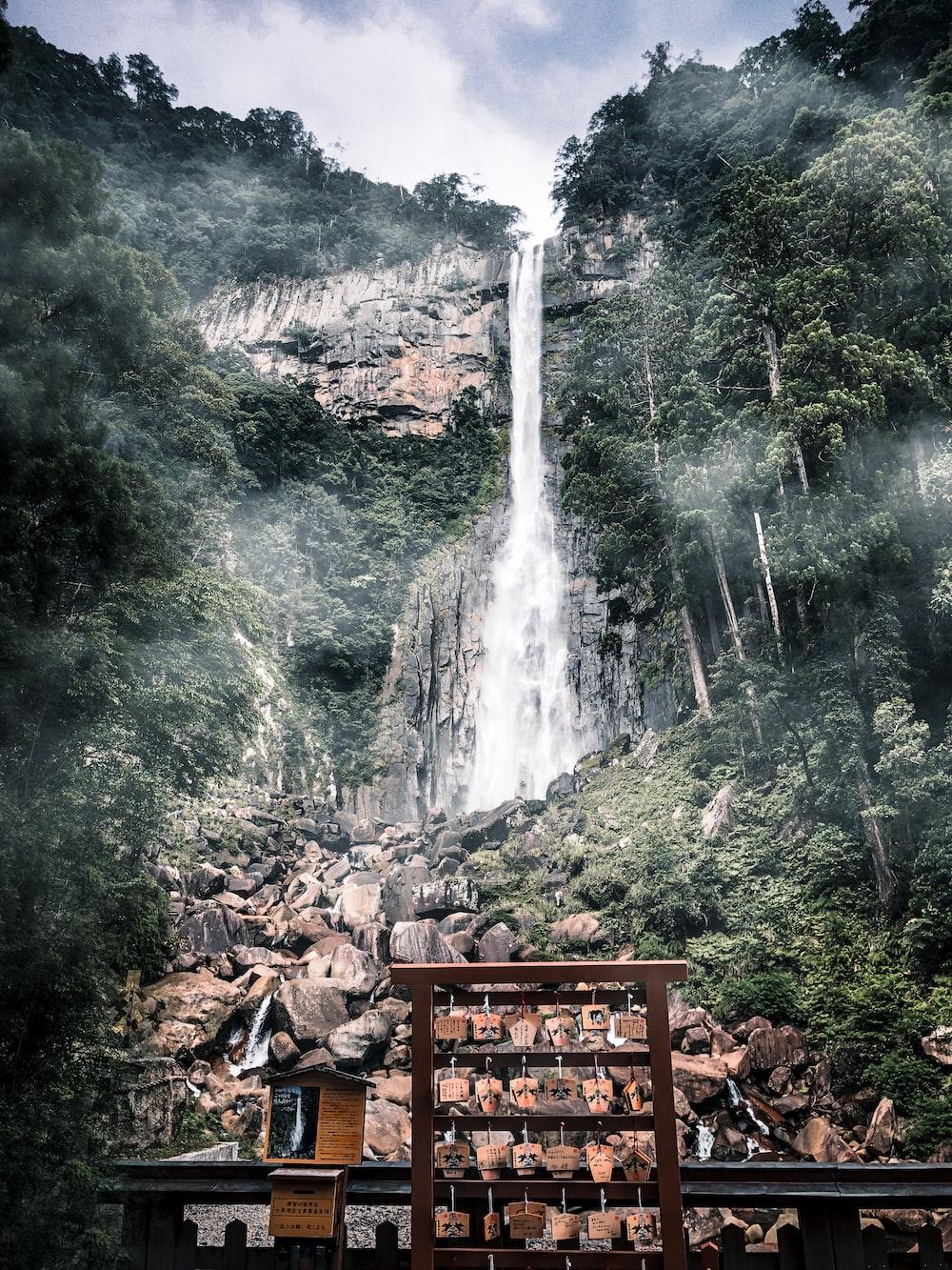 brown wooden bench near waterfalls during daytime
