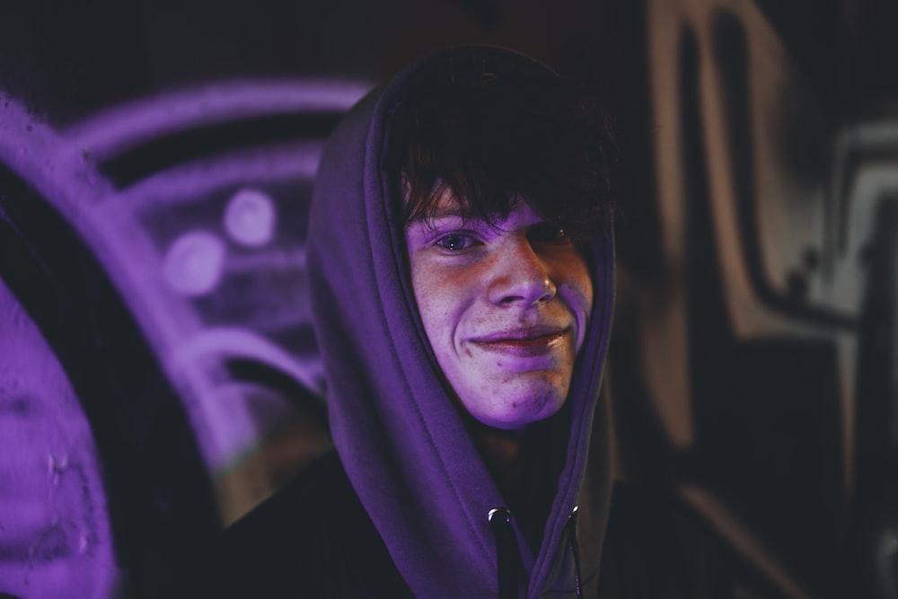 man in black hoodie with purple lights
