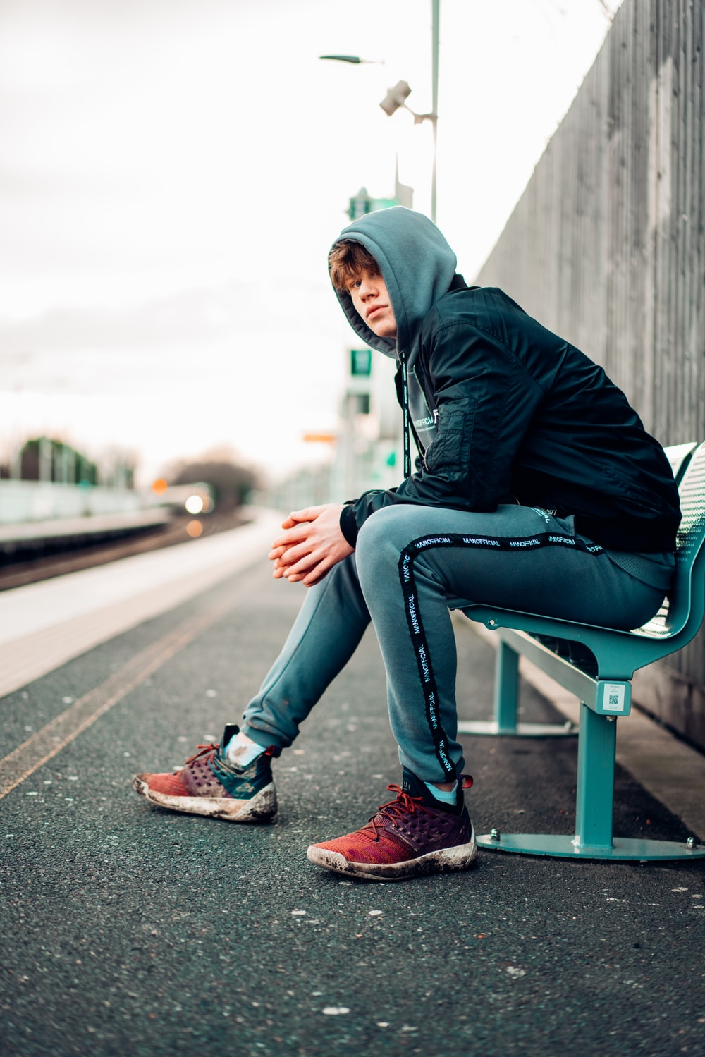 man in black hoodie and blue denim jeans sitting on gray concrete bench during daytime