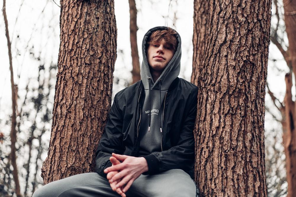 man in black zip up jacket sitting on tree trunk