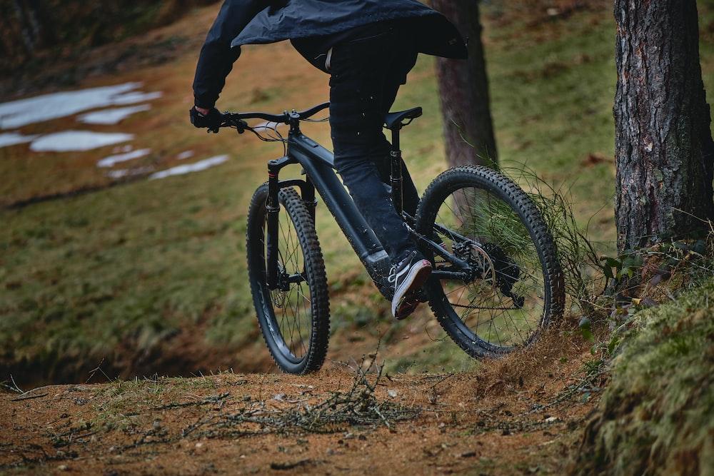 person in black jacket riding black mountain bike