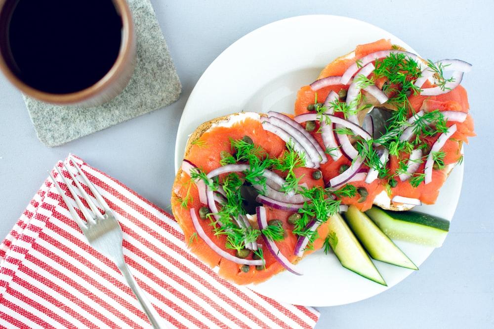 sliced tomato and green vegetable on white ceramic plate