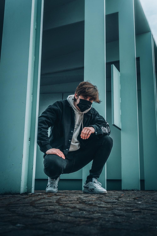 man in black jacket and black pants sitting on blue wooden door