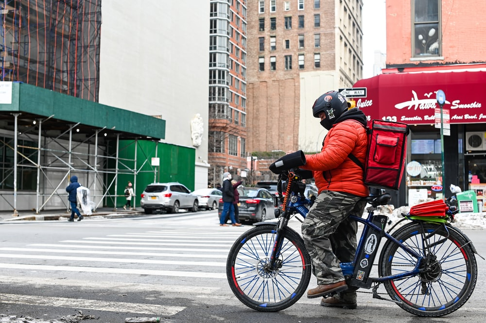 man in blue jacket riding blue motorcycle on road during daytime