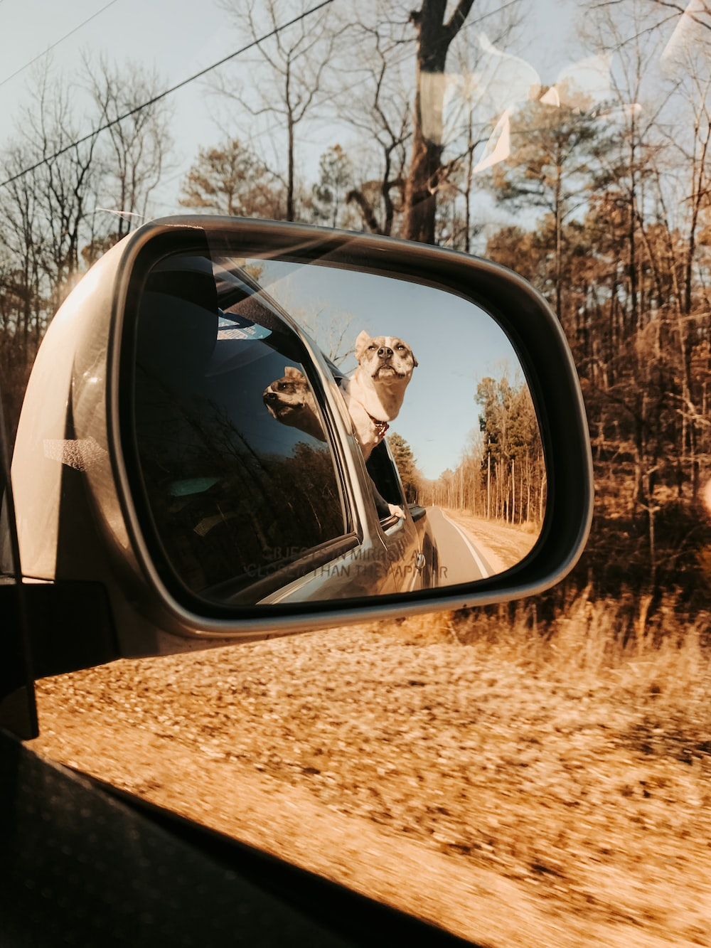 reflection of man in car side mirror