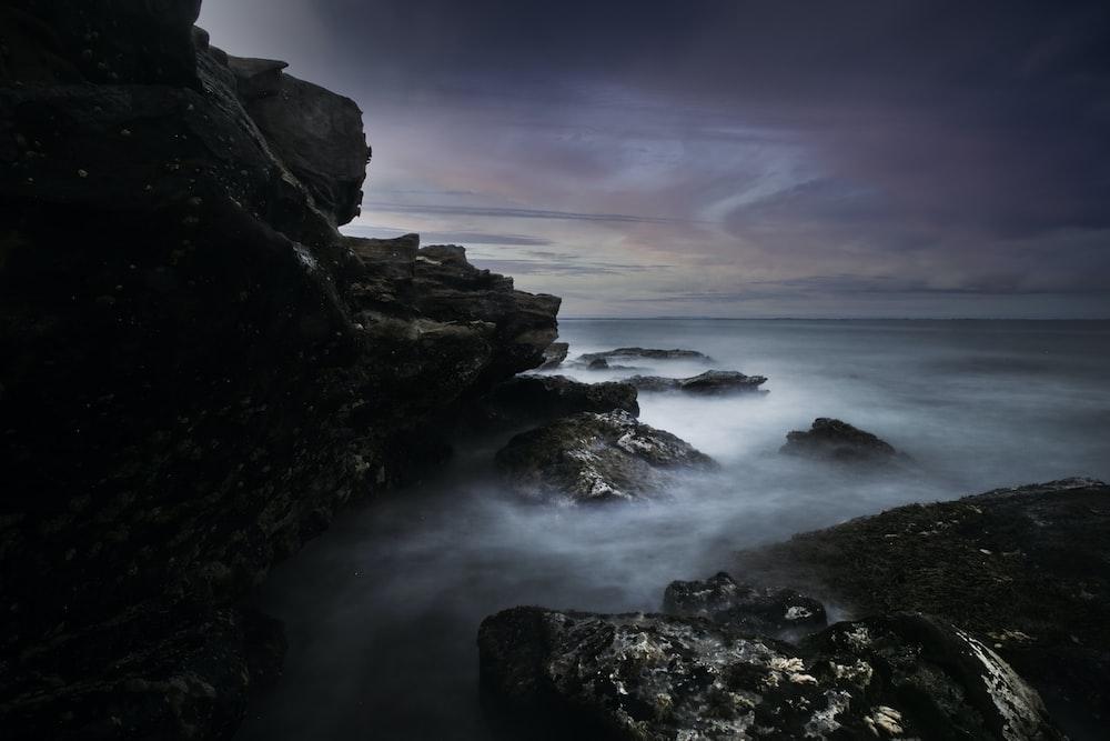 ocean waves crashing on rocks under gray clouds