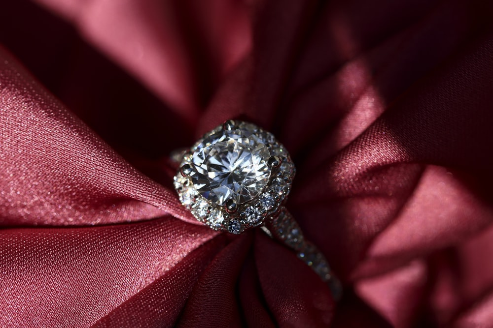 silver diamond ring on red textile
