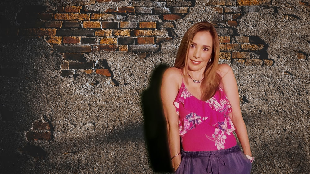 girl in pink tank top and black skirt standing beside brown brick wall