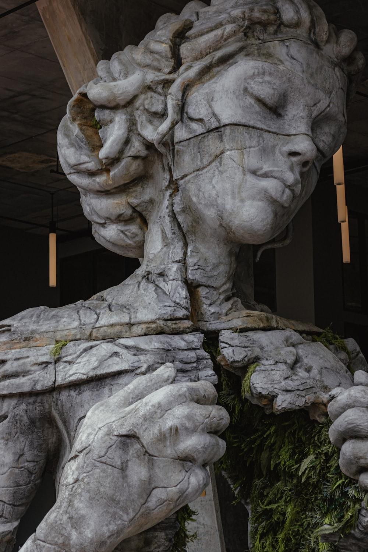 gray concrete statue of man holding stick
