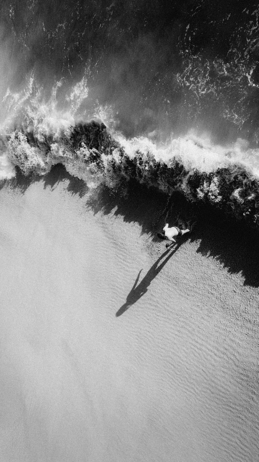 grayscale photo of man in black jacket and pants standing on surfboard