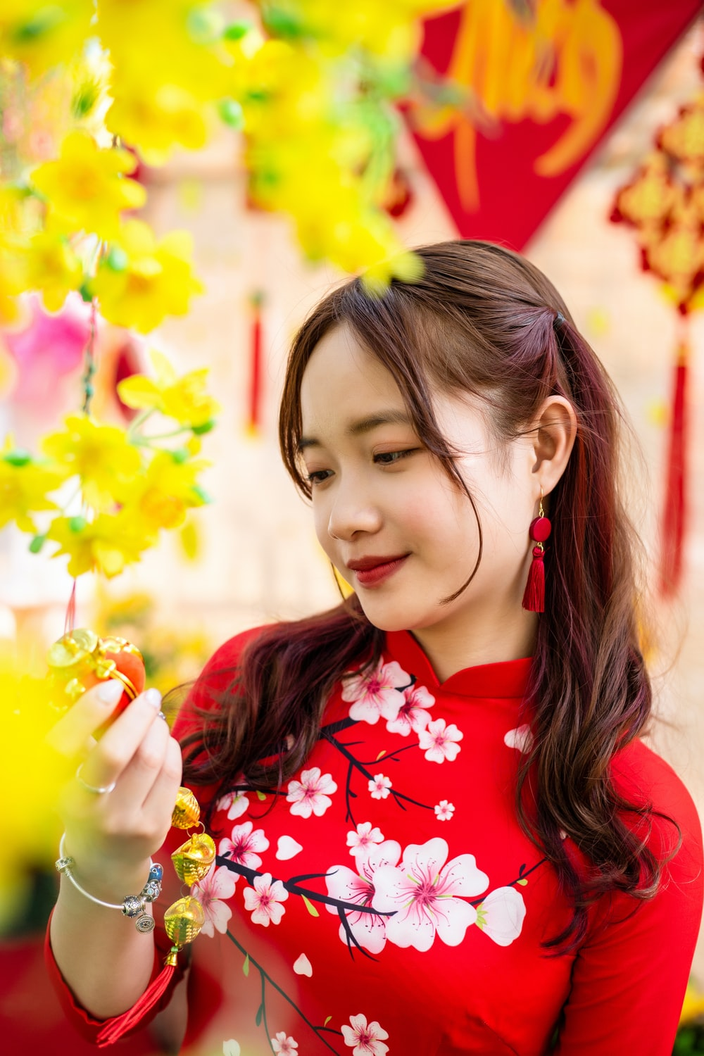 girl in red and white floral shirt holding yellow flower
