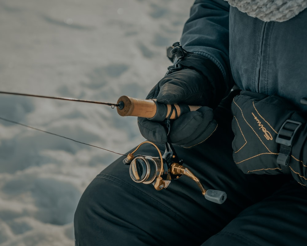 person in black jacket and black pants holding black fishing rod